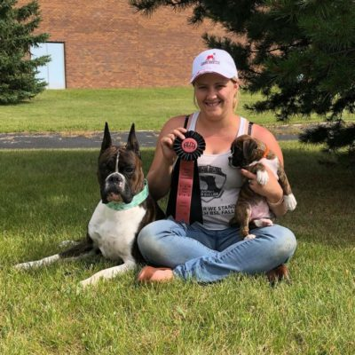Morgan C from Furioso Boxers a CKC boxr breeder with Markus and a boxer puppy at a lure coursing and sprinters event in Alberta Canada